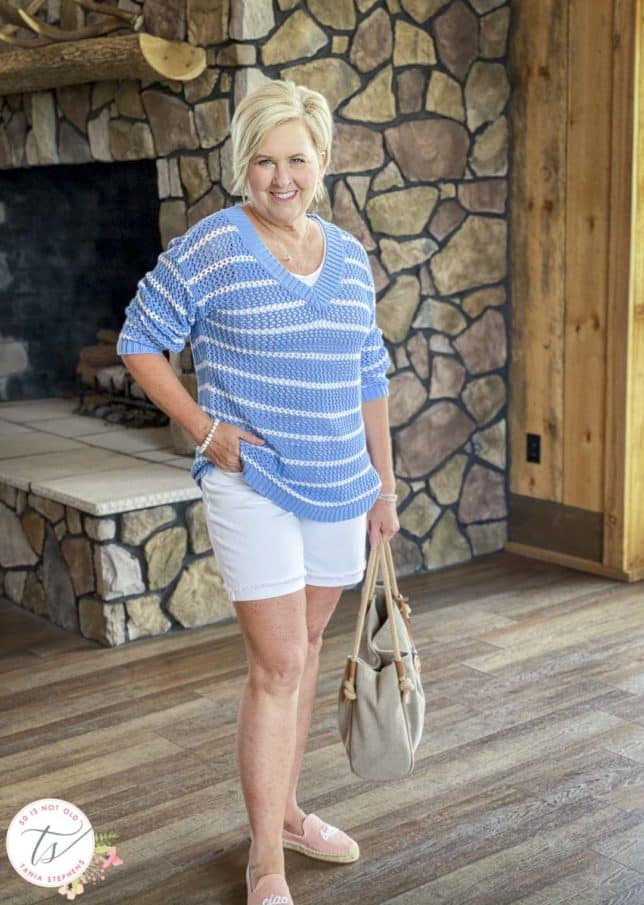 Fashion Blogger 50 Is Not Old is wearing a blue and white striped mesh sweater with white denim shorts, pink espadrilles, and carrying a Michael Kors tote