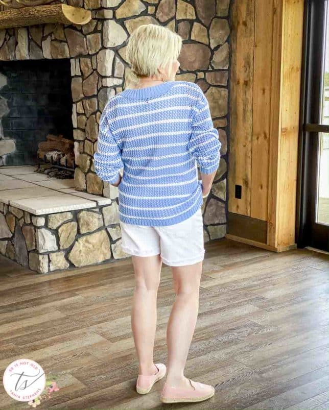 Fashion Blogger 50 Is Not Old is showing the back of a blue and white striped mesh sweater with white denim shorts and pink espadrilles