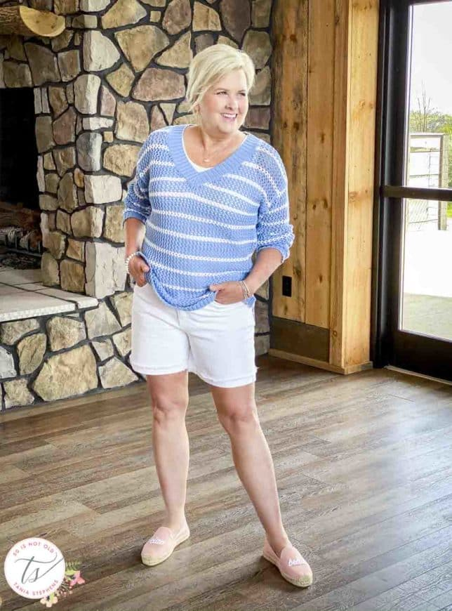 Fashion Blogger 50 Is Not Old is wearing a blue and white mesh sweater with white denim shorts and pink espadrilles