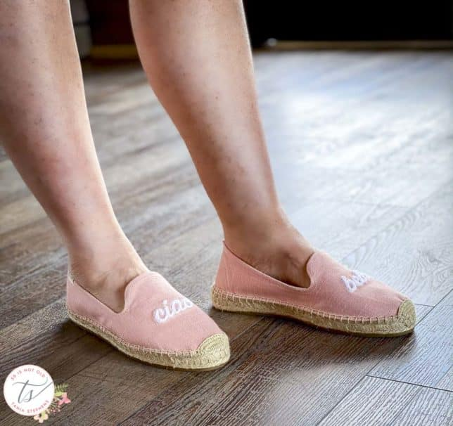 Fashion Blogger 50 Is Not Old is wearing pink espadrilles with the words Ciao Bella embroidered on them