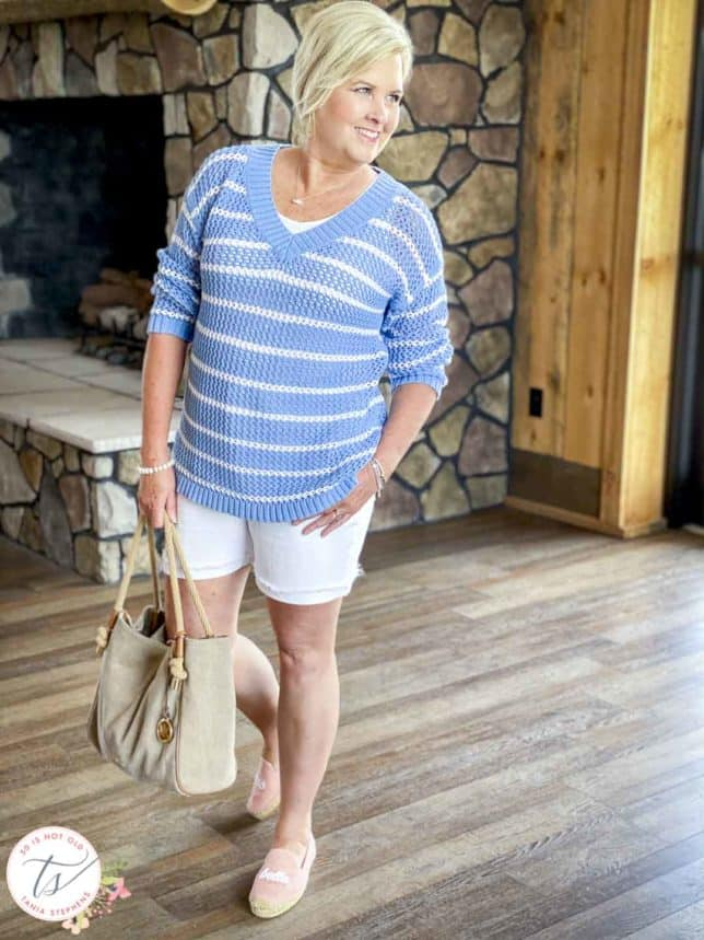 Fashion Blogger 50 Is Not Old is wearing a blue and white striped mesh sweater with white denim shorts, pink espadrilles, and carrying a Michael Kors handbag