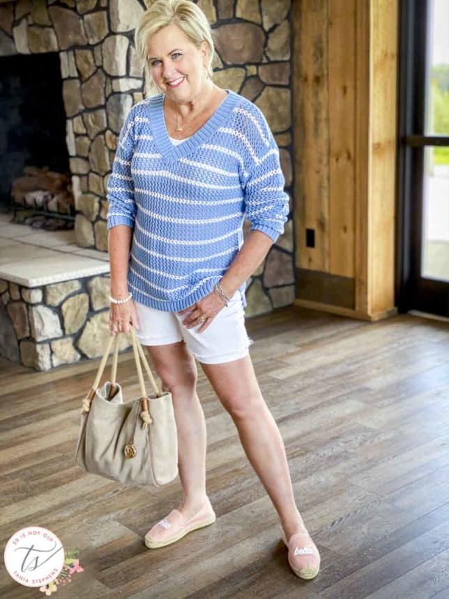 Fashion Blogger 50 Is Not Old is wearing a blue and white mesh sweater with white denim shorts, pink espadrilles, and carrying a Michael Kors tote
