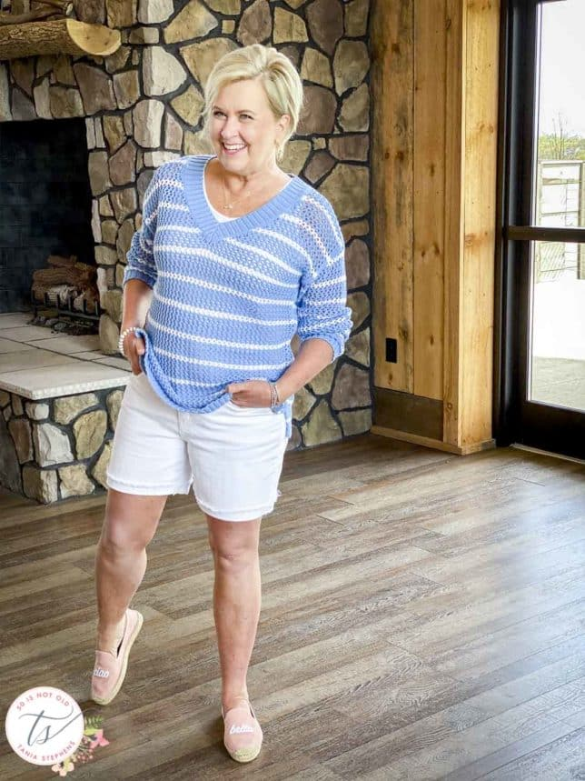 Fashion Blogger 50 Is Not Old is wearing a blue and white striped mesh sweater, white denim shorts, and pink espadrilles