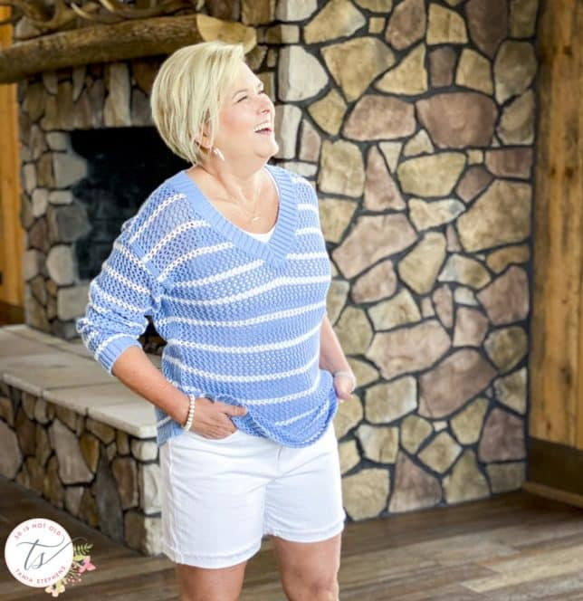 Fashion Blogger 50 Is Not Old is laughing while wearing a blue and white striped mesh sweater with white denim shorts