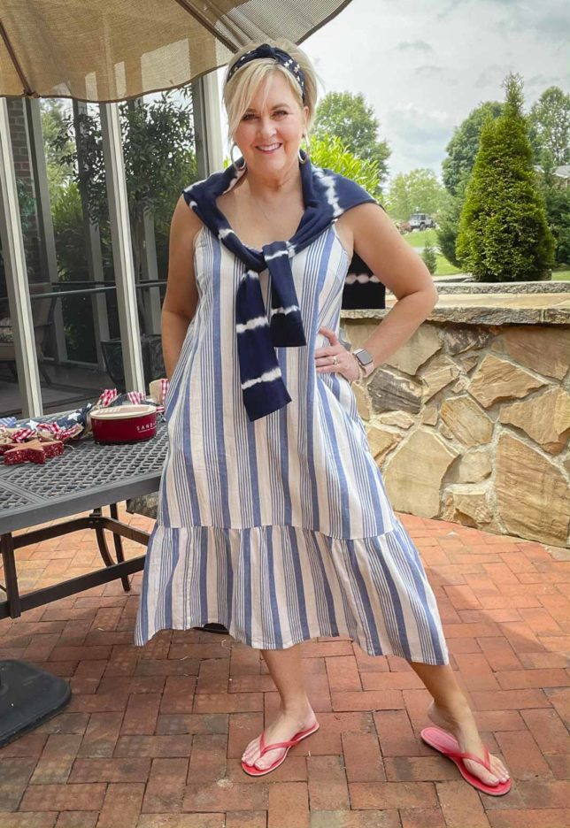 Fashion Blogger 50 Is Not Old is looking festive for the 4th of July in a blue and white striped sundress, a navy headband with stars, red flip-flops, and a navy tie-dyed sweater