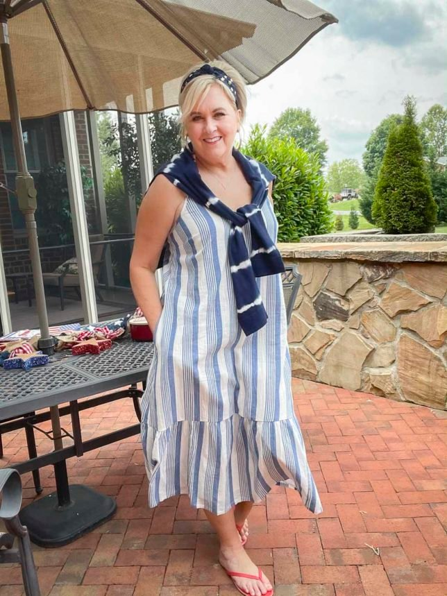 Fashion Blogger 50 Is Not Old is on a patio looking festive for the 4th of July in a blue and white striped sundress, a navy headband with stars, red flip-flops, and a navy tie-dyed sweater