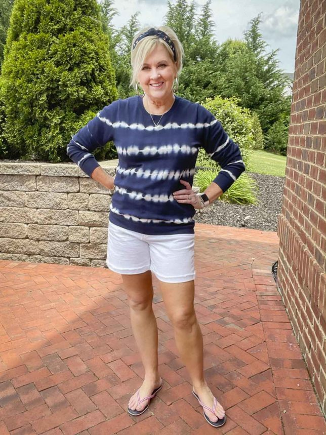 Fashion Blogger 50 Is Not Old is wearing a festive 4th of July outfit of a blue and white tie-dyed sweater, a navy headband with stars, red gingham flip-flops, and white Bermuda shorts