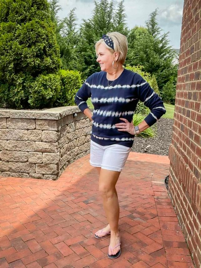 Fashion Blogger 50 Is Not Old is looking festive for the 4th of July in a blue and white tie-dyed sweater, a navy headband with stars, red gingham flip-flops, and white Bermuda shorts