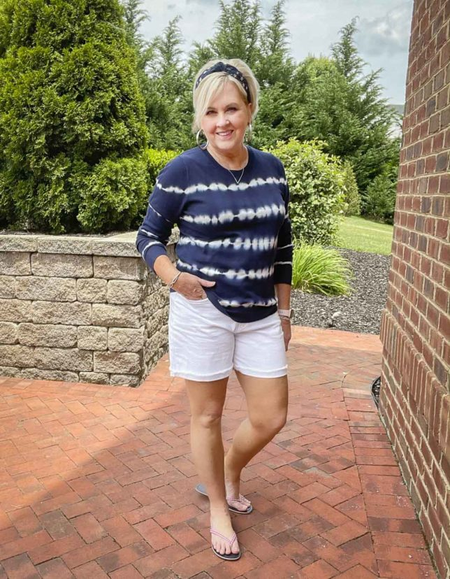 Fashion Blogger 50 Is Not Old is on a patio looking festive for the 4th of July in a blue and white tie-dyed sweater, a navy headband with stars, red gingham flip-flops, and white Bermuda shorts