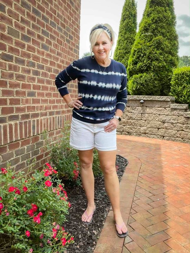 Fashion Blogger 50 Is Not Old is standing by some roses looking festive for the 4th of July in a blue and white tie-dyed sweater, a navy headband with stars, red gingham flip-flops, and white Bermuda shorts