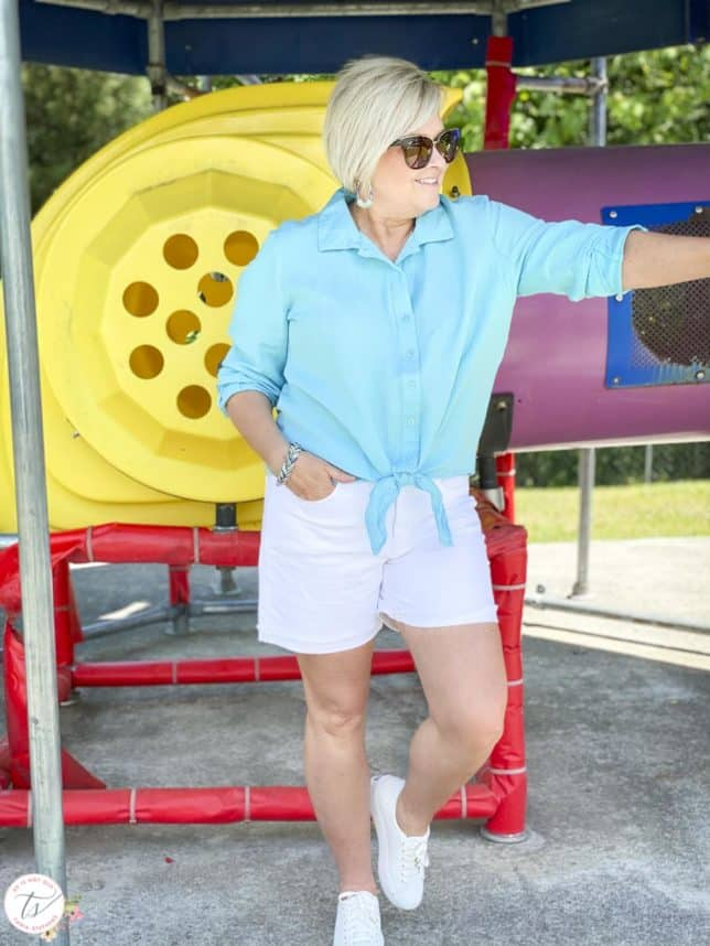 Fashion Blogger 50 Is Not Old is at a playground wearing a blue topaz front tie shirt white white denim shorts and Keds white leather sneakers