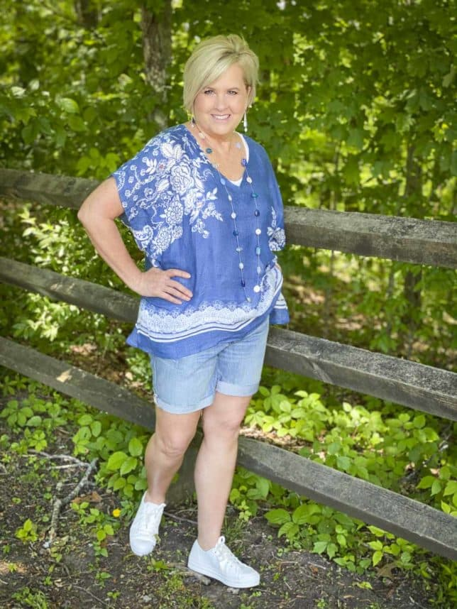 Fashion Blogger 50 Is Not Old is wearing a comfortable poncho with faded denim shorts and white Keds platform sneakers