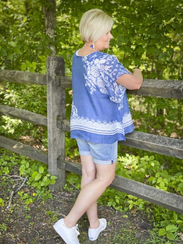 Fashion Blogger 50 Is Not Old is showing the back of a comfortable poncho with denim shorts and white Keds platform sneakers