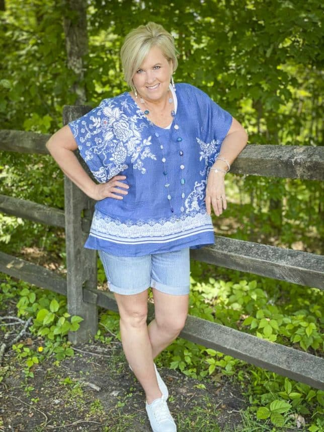 Fashion Blogger 50 Is Not Old is leaning on a fence while wearing a comfortable poncho with denim shorts and white Keds platform sneakers