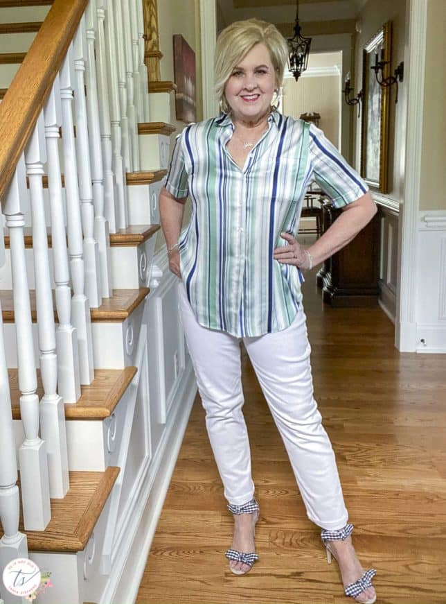 Fashion Blogger 50 Is Not Old is has her hands on her hips while wearing a striped top with white jeans and navy and white gingham heels