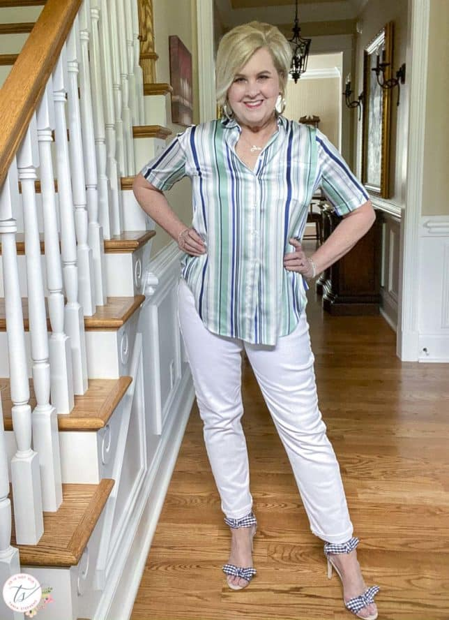 Fashion Blogger 50 Is Not Old is standing beside stairs and wearing a striped top with white jeans and navy and white gingham heels