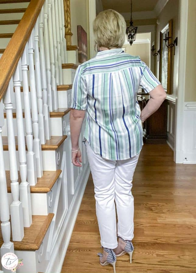 Fashion Blogger 50 Is Not Old is showing the back of a striped top with white jeans and navy and white gingham heels