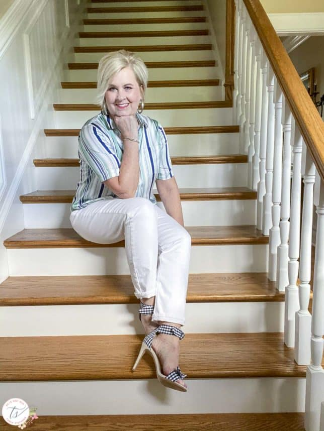 Fashion Blogger 50 Is Not Old is wearing a striped top with white jeans and navy and white gingham heels