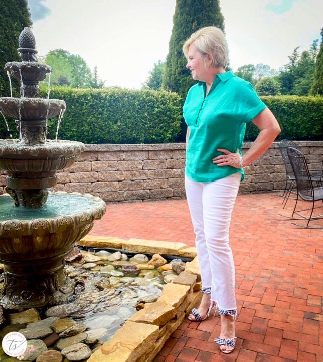 Fashion Blogger 50 Is Not Old is looking at a water fountain while wearing a jade linen pullover shirt with white crop jeans and navy and white gingham heels