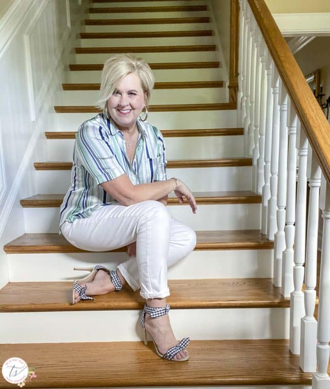Fashion Blogger 50 Is Not Old is wearing a striped top with white jeans and navy and white gingham heels while sitting on stairs