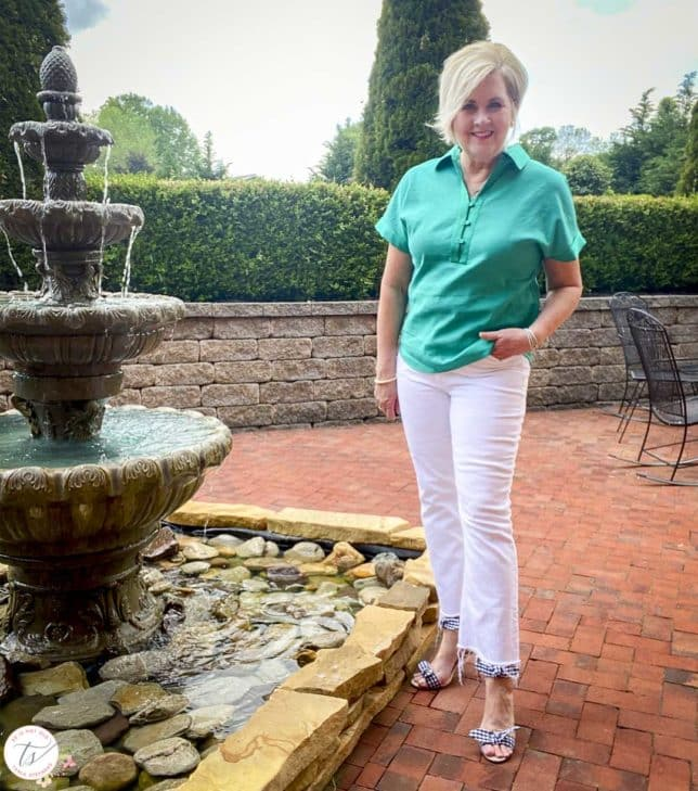 Fashion Blogger 50 Is Not Old is standing by a water fountain while wearing a jade linen pullover shirt with white crop jeans and navy and white gingham heels