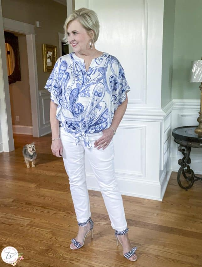 Fashion Blogger 50 Is Not Old is wearing a navy and white paisley tie top with white jeans and navy and white gingham heels