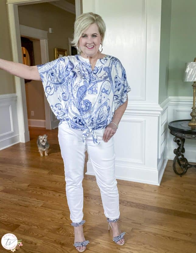 Fashion Blogger 50 Is Not Old is showing the sleeves of a navy and white paisley tie-front top with white jeans and navy and white gingham heels