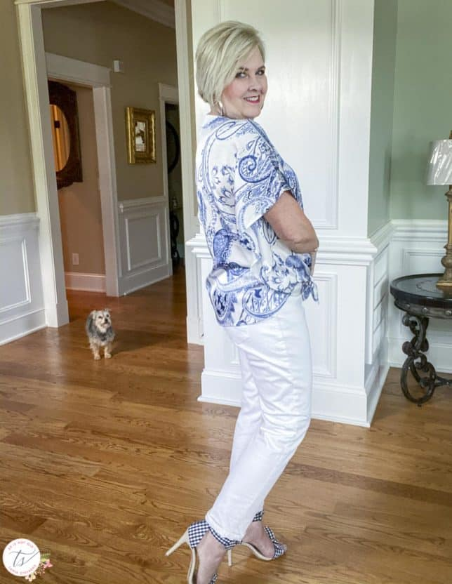 Fashion Blogger 50 Is Not Old is showing the side view of a navy and white paisley tie-front top with white jeans and navy and white gingham heels