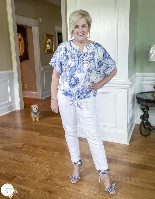 Fashion Blogger 50 Is Not Old is wearing a navy and white paisley tie-front top with white jeans and navy and white gingham heels with her dog looking on