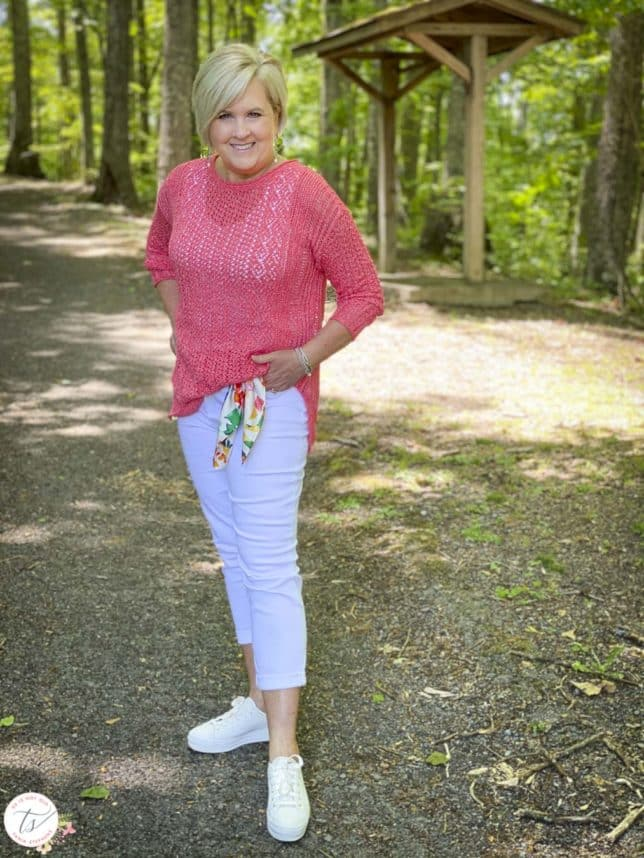 Fashion Blogger 50 Is Not Old is wearing a coral sweater and white jeans