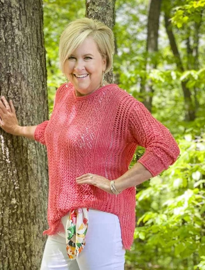 Fashion Blogger 50 Is Not Old is keeping cool in a coral open weave sweater