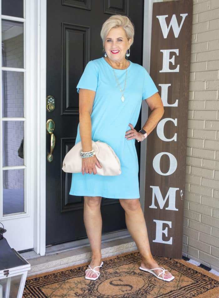 Fashion Blogger 50 Is Not Old is wearing a t-shirt dress with a pouch bag and square toe flip flops