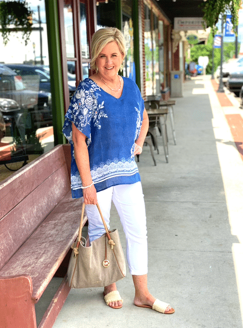 Fashion Blogger 50 Is Not Old is wearing a comfortable poncho with white jenas and raffia sandals while out shopping