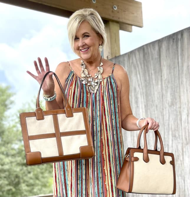 Fashion Blogger 50 Is Not Old is looking vacation ready in a striped maxi dress, and holding two canvas trimmed handbags