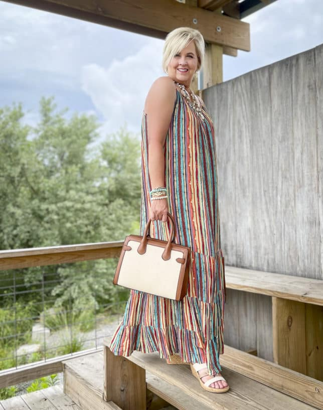 Fashion Blogger 50 Is Not Old is looking vacation ready in a striped maxi dress, and carrying a canvas trimmed bag