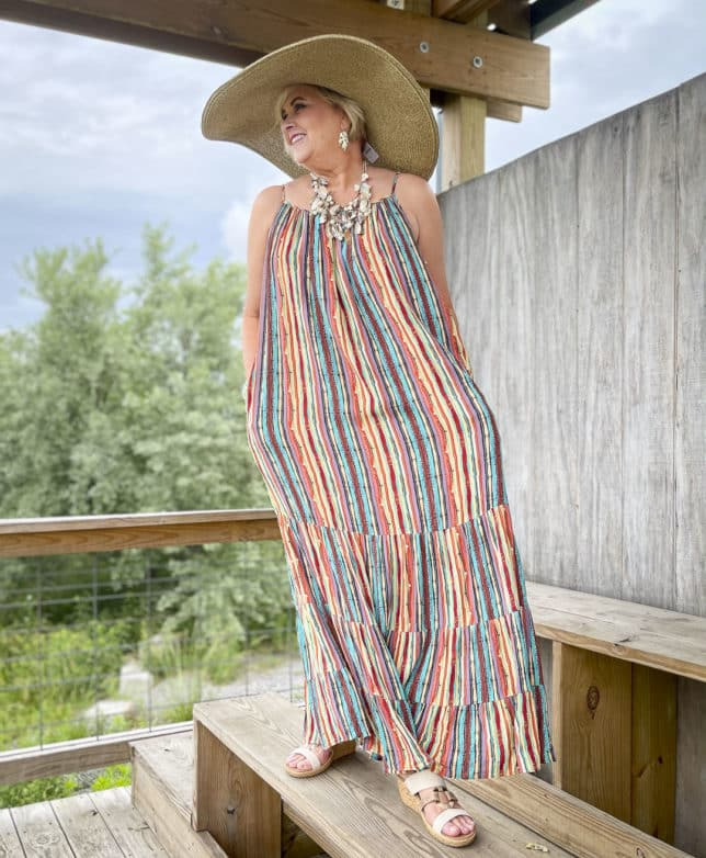 Fashion Blogger 50 Is Not Old is looking vacation ready in a striped maxi dress, a shell necklace, and a large wide brim hat