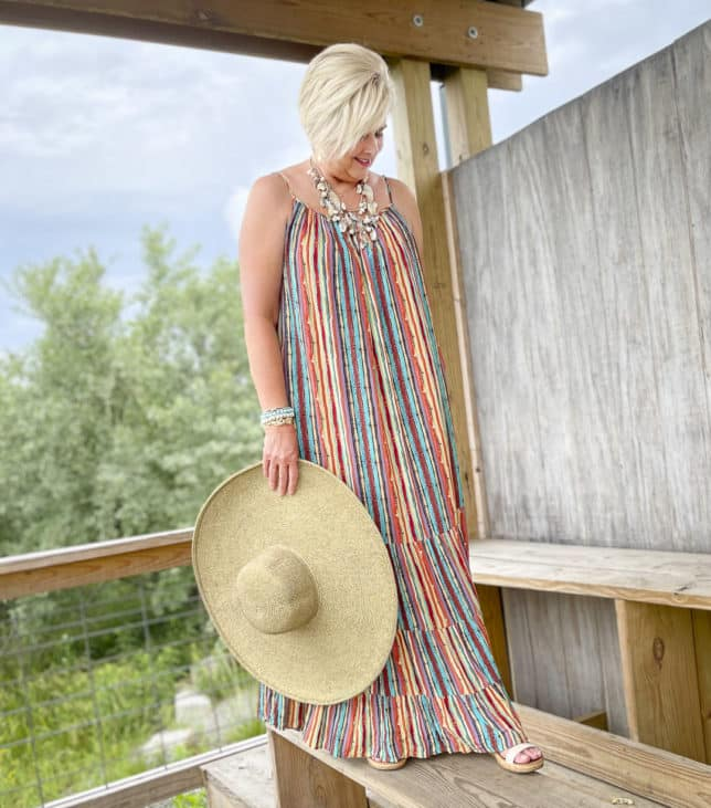 Fashion Blogger 50 Is Not Old is wearing a vacation ready striped maxi dress, a seashell necklace, and a large wide brim hat
