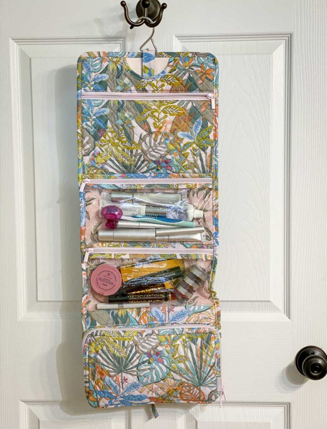 Fashion Blogger 50 Is Not Old is showing her hanging travel organizer Vera Bradley that is full of makeup