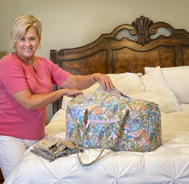 Fashion Blogger 50 Is Not Old is unpacking her traveling duffle bag from Vera Bradley