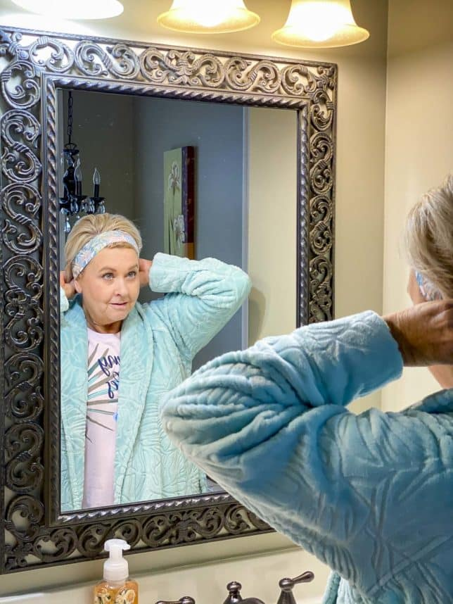 Fashion Blogger 50 Is Not Old is putting a headband on while wearing a robe from Vera Bradley