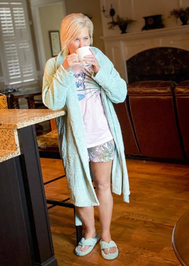 Fashion Blogger 50 Is Not Old is wearing a robe, slippers, and pajamas from Vera Bradley while drinking coffee