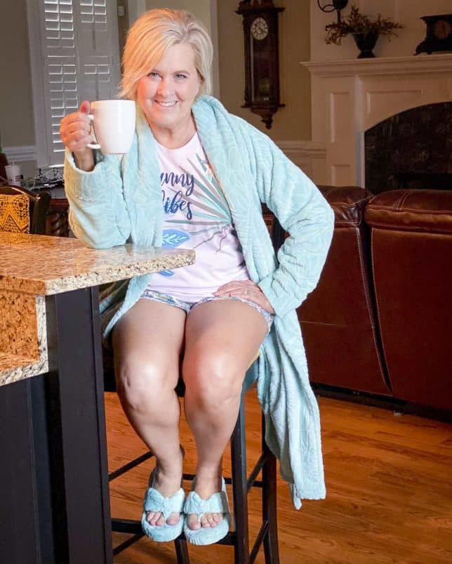 Fashion Blogger 50 Is Not Old is sitting on a bar stool while wearing a robe, slippers, and pajamas from Vera Bradley and drinking coffee