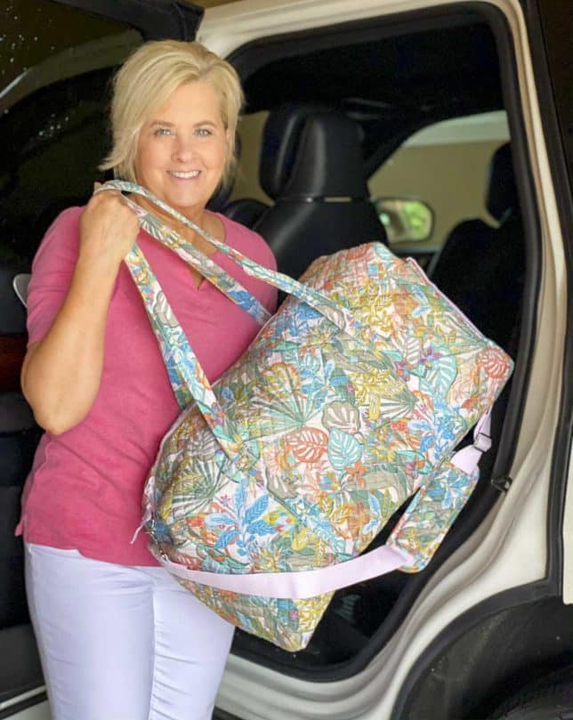 Fashion Blogger 50 Is Not Old is getting her traveling duffle from Vera Bradley out of the car