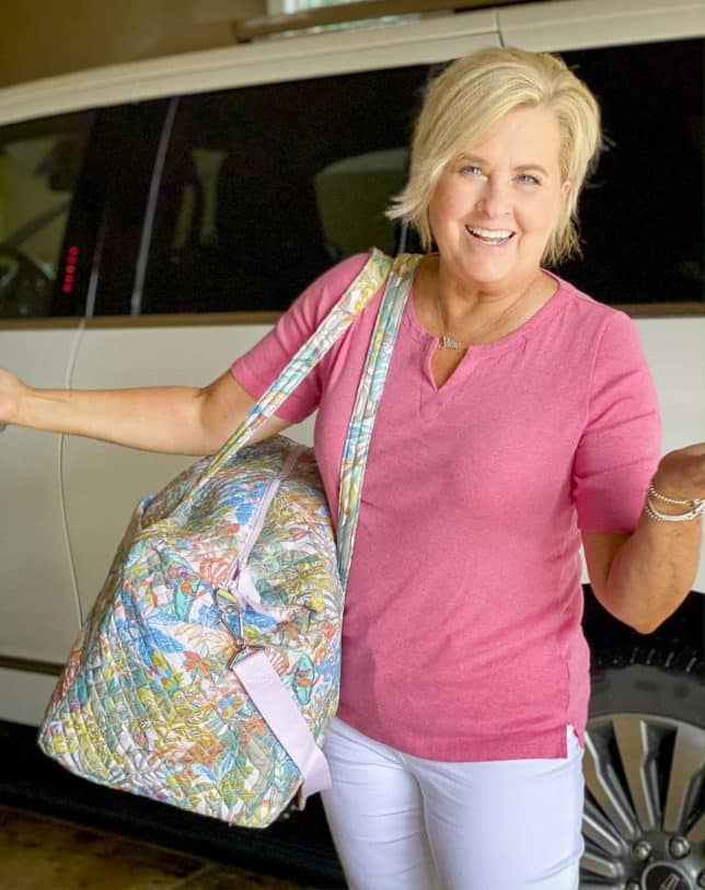 Fashion Blogger 50 Is Not Old is laughing while getting her traveling duffle bag from Vera Bradley out of the car