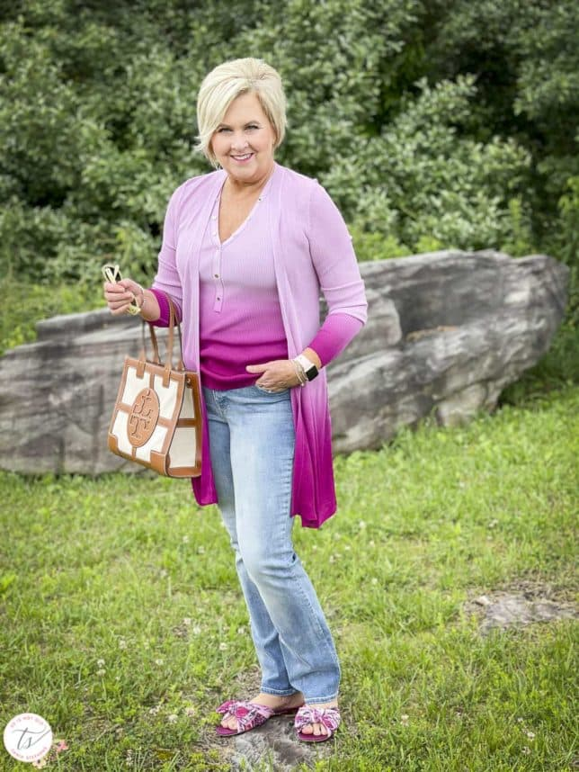 Fashion Blogger 50 Is Not Old is looking colorful in a pink ombre tank and matching coverup, bootcut jeans, floral slides, and is carrying a Tory Burch satchel