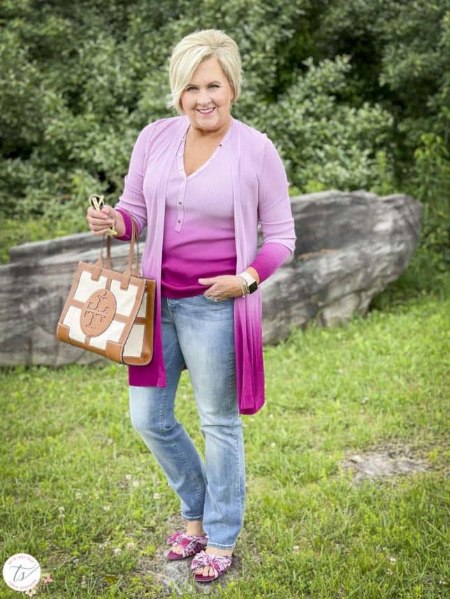 Fashion Blogger 50 Is Not Old is looking colorful in a pink ombre tank and matching coverup, bootcut jeans, pink floral slides, and is carrying a Tory Burch satchel