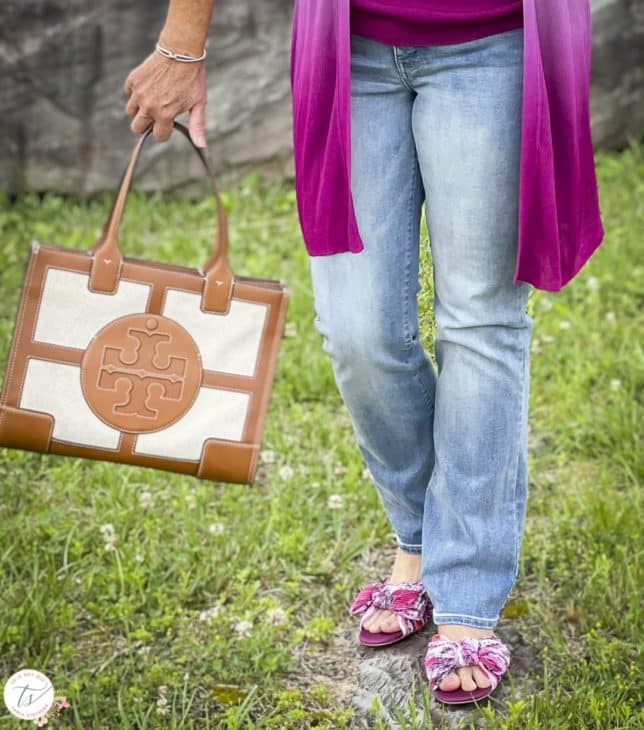 Fashion Blogger 50 Is Not Old is wearing bootcut jeans, pink floral slides, and is carrying a Tory Burch satchel