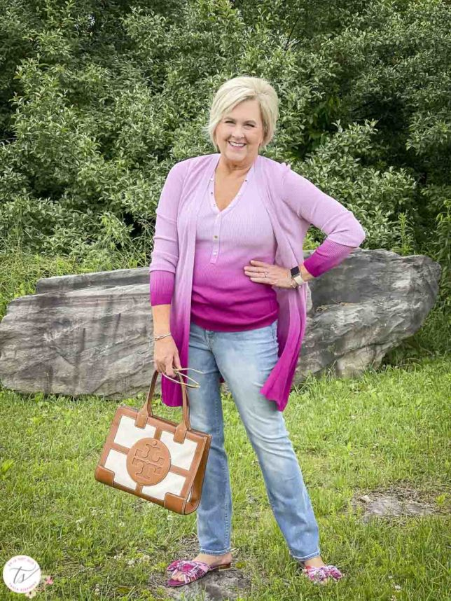 Fashion Blogger 50 Is Not Old is looking colorful in a pink ombre tank and matching coverup, bootcut jeans, pink floral slides, and a Tory Burch satchel