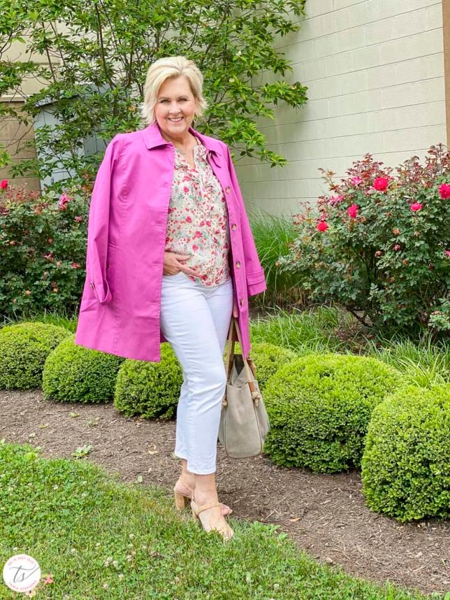 Fashion Blogger 50 Is Not Old is wearing a feminine floral blouse with an orchid trench coat on her shoulders, white crop pants, cork heels, and a Michael Kors handbag