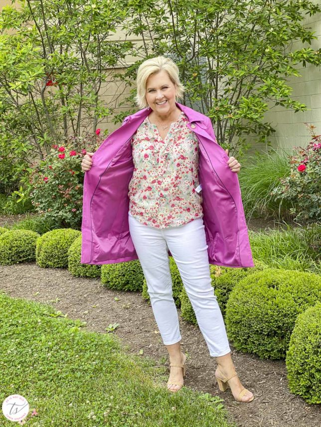Fashion Blogger 50 Is Not Old is showing the lining of an orchid Mac trench coat with a feminine floral blouse, white crop pants, and cork heels